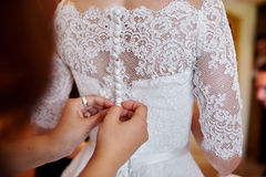 Bridesmaid helping to dress the bride in a wedding morning Royalty Free Stock Photo
