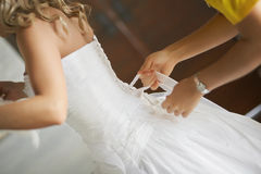 Bridesmaid helping to put brides elegant luxury white dress. Stock Photography