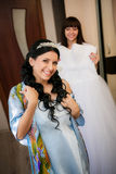 Bridesmaid helps the bride to be prepared for a wedding ceremony Royalty Free Stock Image