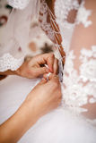 Bridesmaid helps bride to put on a wedding dress. Royalty Free Stock Image
