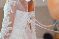 Bridesmaid helps bride to wearing wedding dress, close-up back view Royalty Free Stock Photos