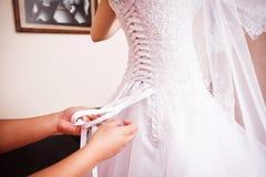 Bridesmaid helps to bride Stock Image