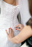 Bridesmaid helps to bride to put on a wedding dress. Royalty Free Stock Photo