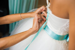 Bridesmaid helps to tie a bow on a festive white dress of the bride on the wedding day Stock Images