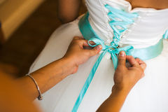Bridesmaid helps to tie a bow on a festive white dress of the bride on the wedding day