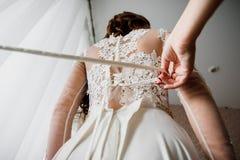 Bridesmaid helps to tie ribbon on white elegant wedding dress Royalty Free Stock Photography