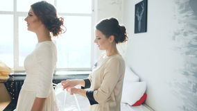 Bridesmaid helps zip up wedding dress for beautifull bride on marriage day stock video