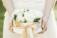 Bridesmaid holding a box of roses. Rose box. Beautiful gift with white roses. Royalty Free Stock Photo