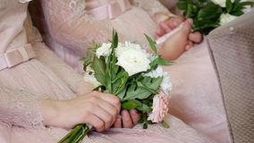 Bridesmaid holding wedding bouquet against dress stock video