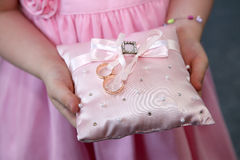 Bridesmaid holds a decorative cushion with wedding gold rings