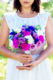 Bridesmaid holds a wedding bouquet of roses in purple tones. Flo Stock Photography