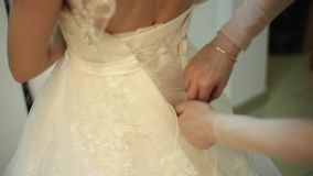 Bridesmaid is lacing wedding dress for beautiful yaung woman in bridal boutique, concept of preparing wedding stock footage