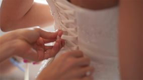 Bridesmaid is lacing white wedding dress for beautiful bride,preparing wedding stock footage