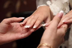 Bridesmaid looks at the manicure of the bride Stock Images