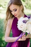 Bridesmaid with luxurious colorful wedding bouquet of peonies and other flowers with professional makeup standing at the Royalty Free Stock Photography