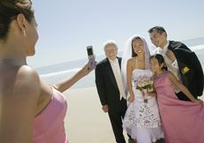 Bridesmaid photographing newly weds with family on beach Royalty Free Stock Images