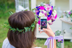 Bridesmaid photographing a wedding bouquet on the phone. Florist. Ic composition in vintage style. The Provence Royalty Free Stock Photos