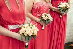 Bridesmaid the same dressed with bouquets of roses and other flo Royalty Free Stock Photography