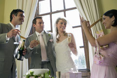 Bridesmaid taking photograph of bride, groom, and usher with champagne, smiling, low angle view Royalty Free Stock Images