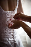 Bridesmaid tie the laces on the back of a wedding dress Stock Image
