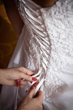Bridesmaid tie the laces on the back of a wedding dress Royalty Free Stock Photography