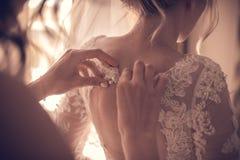 Bridesmaid tying bow on wedding dress royalty free stock image