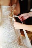 Bridesmaid tying bow on wedding dress Royalty Free Stock Photo