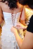 Bridesmaid tying bow on wedding dress Stock Photography