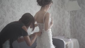 Bridesmaid tying bow on wedding dress. Bride getting ready for the wedding ceremony. Wedding dress close-up stock footage