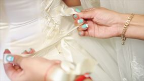 Bridesmaid tying bow on wedding dress. Hd stock footage