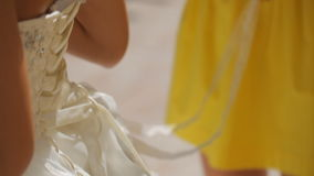 Bridesmaid tying bow on wedding dress. Bridesmaid is helping the bride to dress stock footage