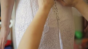 Bridesmaid tying bow on wedding dress. In room bride stock video