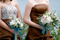 The bridesmaids. Bridesmaids standing at the wedding ceremony holding bouquets stock image