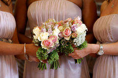 Bridesmaids. Three bridesmaids holding flower bouquet. Narrow depth of field (sharp focus on the flower bouquet Royalty Free Stock Photo