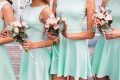 Bridesmaids in aqua. With wedding white bouquet royalty free stock image