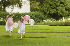 Bridesmaids With Balloons Running In Garden Stock Image