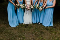 Bridesmaids in blue. Five brides maids with blue gowns and colorful flowers royalty free stock photo