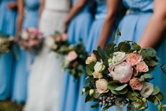 Bridesmaids in blue. Five brides maids with blue gowns and colorful flowers stock image