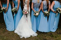 Bridesmaids in blue. Five brides maids with blue gowns and colorful flowers. View from the back royalty free stock photography