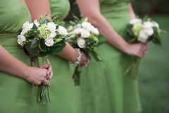 Bridesmaids bouquets. Row of bridesmaids holding green bouquets at wedding royalty free stock photography