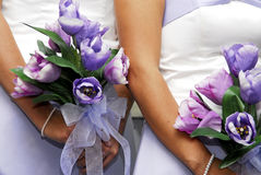 Bridesmaids Bouquets. Closeup of two bridesmaids' bouquets of purple and pink flowers, being held by the women during a wedding ceremony Royalty Free Stock Image