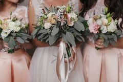 Bridesmaids and bride holding modern wedding bouquets of pink roses and green eucalyptus with pink ribbons. Stylish Contemporary. Bouquets on soft fabric stock image