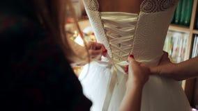 Bridesmaids buttoning on wedding dress stock video