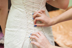 Bridesmaids dress laces on the back of a bride stock photos