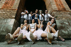 Bridesmaids in the glamorous dresses and the groomsmen stock image