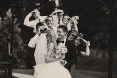 Bridesmaids and groomsmen look at a kissing wedding couple stand Stock Photography