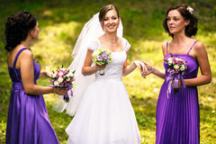 Bridesmaids help bride to put on earrings and necklace Stock Photos