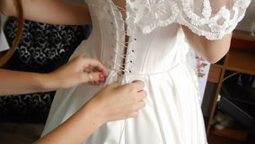 Bridesmaids help the bride to wear a wedding dress stock video footage