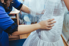 Bridesmaids help dress bride gown. Royalty Free Stock Photo