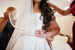 Bridesmaids helped dressed wedding dress for bride at room. Stock Photos